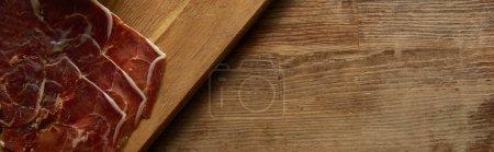Foto de Vista superior de la prosciutto cortada en el tablero de corte sobre fondo de madera, tiro panorámico. - Imagen libre de derechos