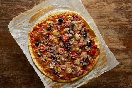 Foto de Vista superior de la deliciosa pizza con tomates de cerezo, aceitunas y parmesano en papel de pergamino sobre fondo de madera. - Imagen libre de derechos