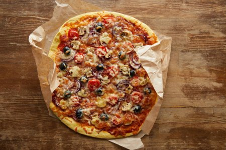 Foto de Vista superior de la deliciosa pizza en papel de pergamino sobre fondo de madera. - Imagen libre de derechos