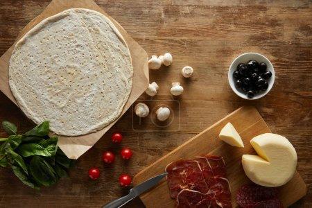 Ansicht von rohem Teig, Kirschtomaten, Basilikum, Pilzen, Oliven, Mozzarella, Salami und Prosciutto für Pizza auf Holztisch