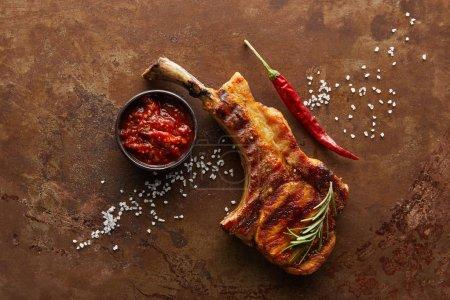Photo pour Vue du dessus du steak de côtelette avec sauce tomate, romarin et piment sur la surface de la pierre - image libre de droit