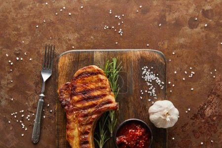 Photo for Top view of grilled steak with tomato sauce and garlic on cutting board by fork on stone background - Royalty Free Image