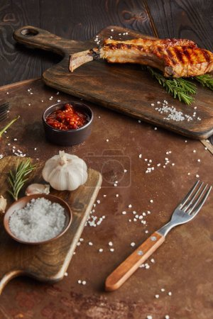 Selective focus of delicious ribeye steak on cutting board with garlic and tomato sauce on stone board on wooden surface