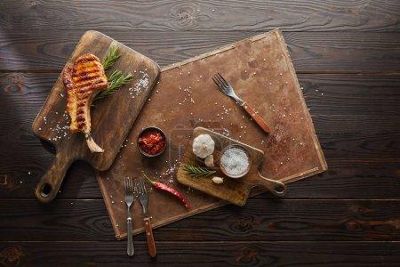 Photo pour Vue en haut d'un délicieux steak sur une planche à découper avec sauce chili, romarin et sel sur une planche en pierre sur fond en bois - image libre de droit