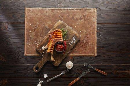 Photo pour Vue supérieure d'un steak de ribeye grillé avec de l'ail, du romarin et de la sauce chili sur un panneau de pierre sur fond en bois. - image libre de droit