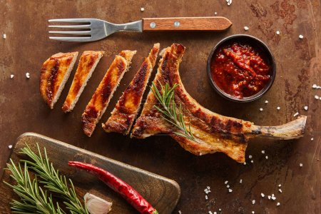 Photo pour Vue du dessus du steak de côtelette tranché avec sauce chili, romarin et ail à la surface de la pierre - image libre de droit