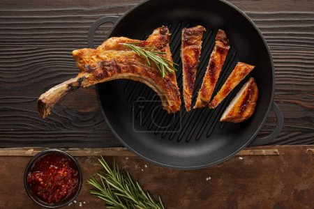 Top view of sliced ribeye steak in frying pan with tomato sauce and rosemary on wooden surface on stone background