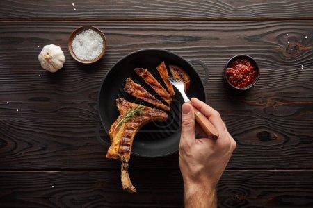 Photo pour Vue de dessus de l'homme tenant fourchette avec tranche de steak à la sauce tomate, sel et ail sur fond en bois - image libre de droit