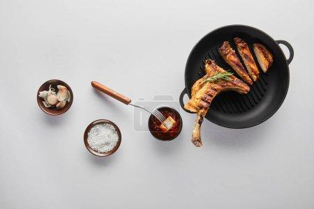 Photo pour Vue du dessus du steak de côtelette grillé avec sauce tomate, ail et sel sur fond blanc - image libre de droit