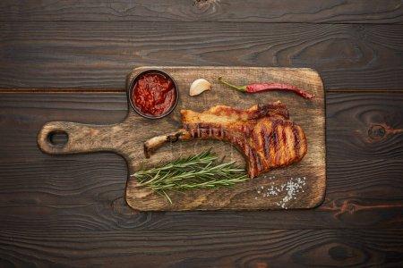 Photo pour Vue du dessus du steak de côtelette gastronomique avec sauce chili, ail et romarin sur planche à découper sur fond bois - image libre de droit