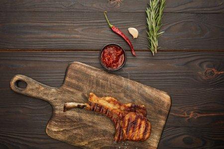 Photo pour Vue du dessus de délicieux steak de côtelette sur planche à découper avec sauce chili, romarin et ail sur fond en bois - image libre de droit