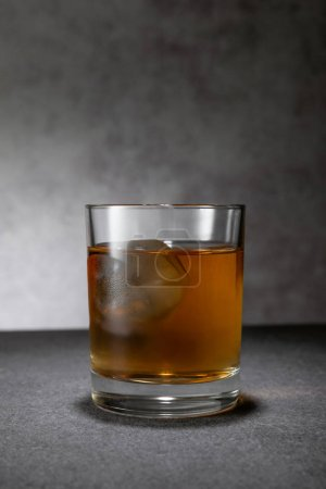 Photo for Frozen ice cube in glass of whiskey on grey - Royalty Free Image