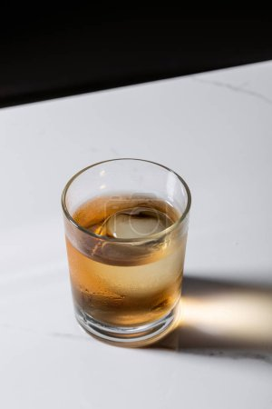 glaçon dans un verre de whisky isolé sur noir