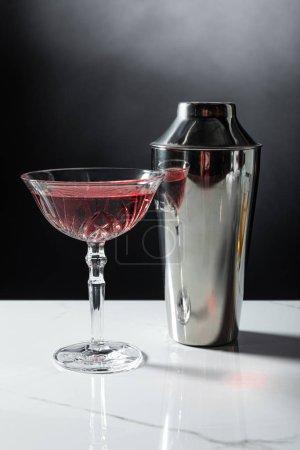 verre avec vin rouge près shaker sur noir