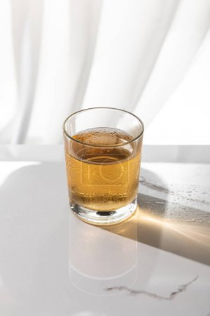 Photo for Glass of whiskey on white marble surface - Royalty Free Image