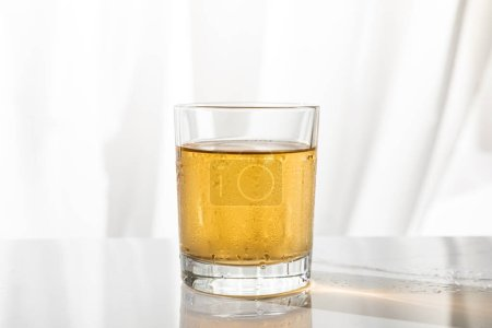 Photo for Wet glass of strong whiskey on white with copy space - Royalty Free Image