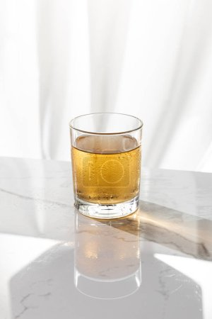 wet glass with strong whiskey on white with copy space