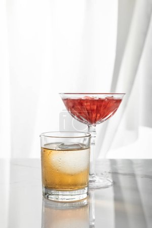 glass of strong whiskey near red cocktail on white