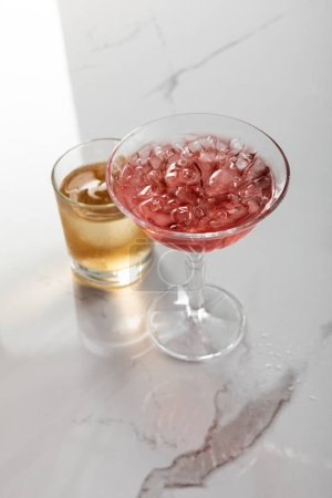 Photo for Glass of brandy near red cocktail with ice cubes on white marble surface - Royalty Free Image