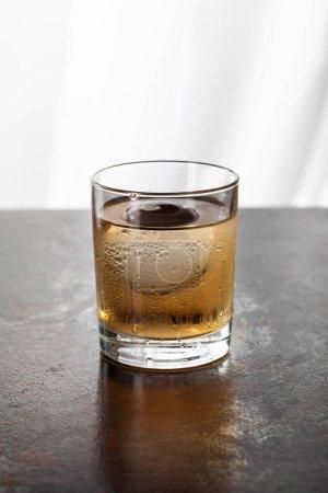 Photo pour Verre mouillé avec whisky et glaçon sur blanc - image libre de droit