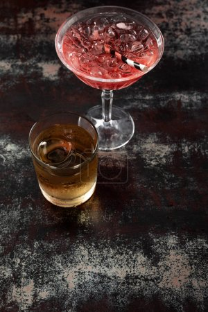 Photo pour Top view of cosmopolitan cocktail near glass with whiskey on black surface - image libre de droit