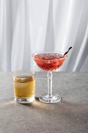 Photo pour Verre avec whisky et glace près de cocktail cosmopolite rouge sur blanc - image libre de droit
