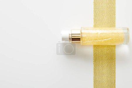 Vue du dessus de bouteille d'huile cosmétique sur bande dorée sur fond blanc