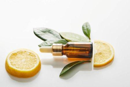 Photo pour Vue du dessus de la bouteille d'huile cosmétique avec des feuilles et des tranches de citron sur fond blanc, panoramique - image libre de droit