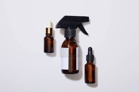 Top view of dispenser cosmetic bottles of oil on grey background