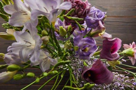 Photo pour Mise au point sélective de bouquet floral violet et violet sur table en bois - image libre de droit