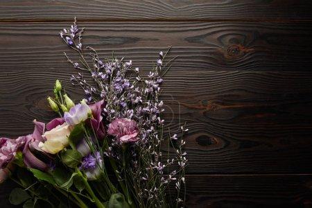 Foto de Vista superior del ramo floral violeta y púrpura sobre la mesa de madera. - Imagen libre de derechos