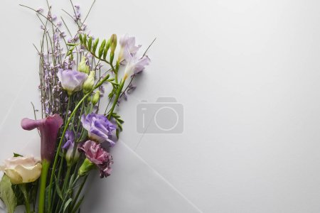 Photo for Top view of violet bouquet wrapped in paper on white background - Royalty Free Image