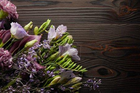 Photo pour Top vue du bouquet floral violet et violet sur table en bois - image libre de droit
