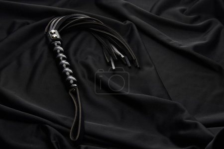 leather flogging whip on black textile background