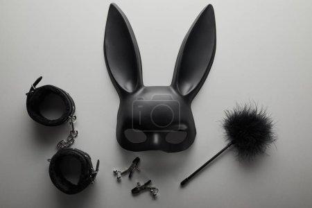 Photo pour Vue du dessus du masque noir de lapin et des jouets sexuels sur fond blanc - image libre de droit