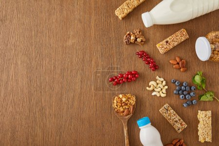 Photo for Top view of berries, nuts, cereal bars and bottles of yogurt and milk on wooden background - Royalty Free Image