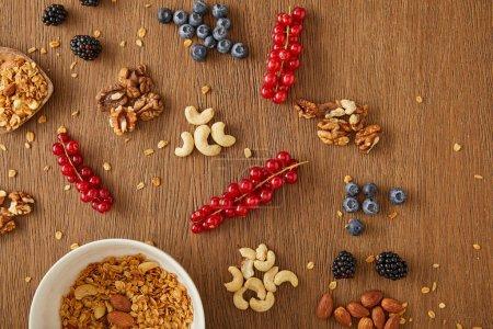 Photo pour Vue du haut du bol avec du granola à côté des baies, des noix et des barres céréalières sur fond de bois - image libre de droit