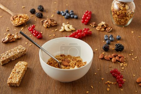 Photo for Jar and bowl with granola next to berries, nuts, cereal bars on wooden background - Royalty Free Image