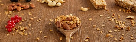 Wooden spatula with granola next to redcurrants, nuts and cereal bars on wooden background, panoramic shot
