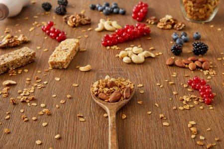 Photo pour Spatule en bois avec granola à côté de baies, noix, flocons d'avoine et barres de céréales sur fond en bois - image libre de droit