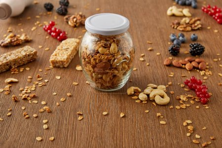 Selective focus of jar of granola with nuts, oat flakes, berries and cereal bars on wooden background