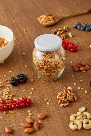 Jar of granola, bowl and spatula next to almonds, walnuts, cashews, berries on wooden background
