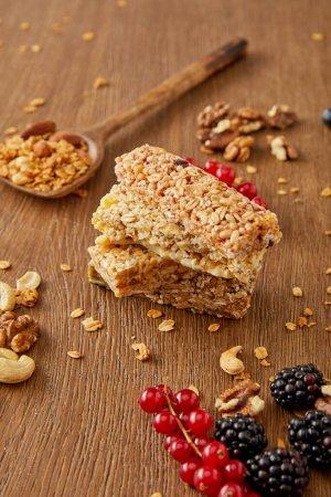 Photo pour Mise au point sélective de barres céréalières, spatules avec granola et groseilles, mûres, noix de cajou, noix sur fond de bois - image libre de droit