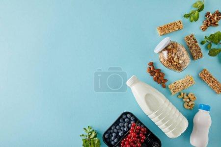 Photo pour Vue du haut du récipient avec baies, bouteilles de yogourt et lait, pot de granola, noix, barres céréalières sur fond bleu - image libre de droit