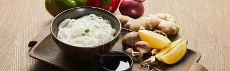 Photo pour Nouilles de riz dans un bol près de la sauce soja, racine de gingembre, oignon et champignons sur plateau en bois, plan panoramique - image libre de droit