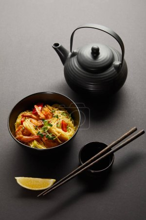 Photo for Noodles with shrimps and vegetables in bowl near lemon, teapot, wooden chopsticks and soy sauce on black background - Royalty Free Image