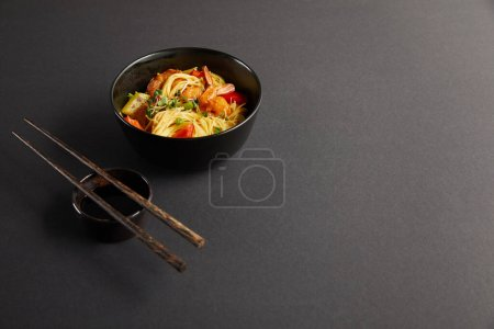 Photo for Noodles with shrimps and vegetables in bowl near wooden chopsticks and soy sauce on black background - Royalty Free Image