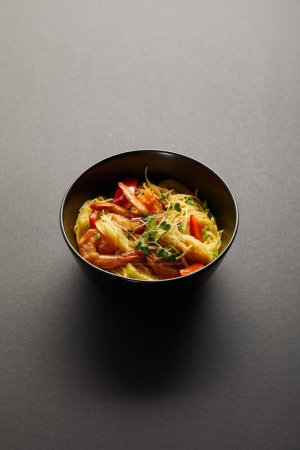 noodles with shrimps and vegetables in bowl on black background