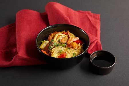 noodles with shrimps and vegetables in bowl near soy sauce on red napkin on black background