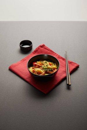 Photo pour Nouilles aux crevettes et légumes dans un bol près de baguettes en bois, sauce soja sur serviette rouge sur fond noir - image libre de droit